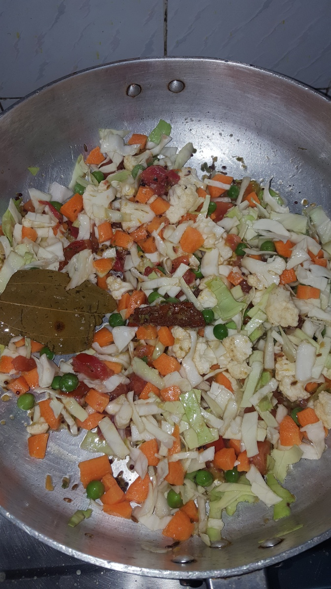 Add the chopped vegetables once the tomatoes are halfy cooked