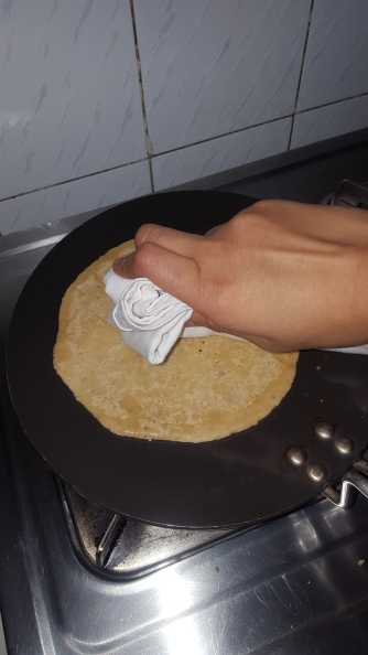 Flip the roti and press with the cloth