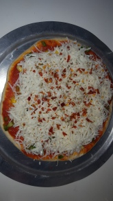 Add oregano and red chilli flakes on top of the cheese